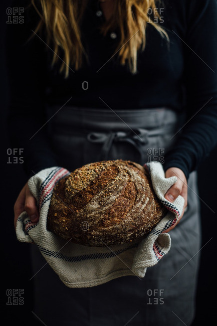 Woman holding a round bread loaf
