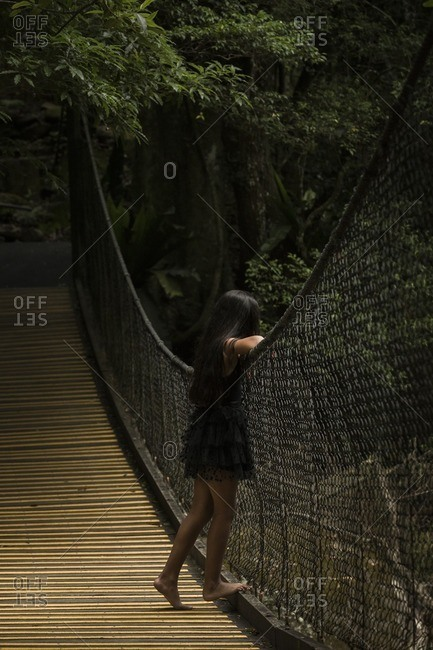 Girl on a swinging bridge looking at nature