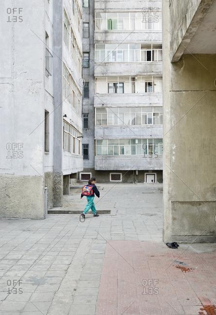 Pyongyang, North Korea - May 3, 2007: Girl walking between apartment blocks in Pyongyang