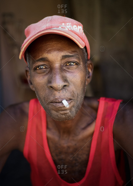 Havana, Cuba,  - August 23, 2016: Portrait of a man wearing red hat and shirt and smoking