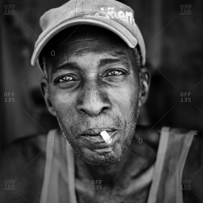 Havana, Cuba,  - August 23, 2016: Portrait of a man wearing red hat and shirt and smoking in black and white