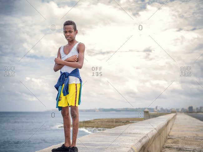 Havana, Cuba,  - August 31, 2016: Boy standing by the sea on the coast