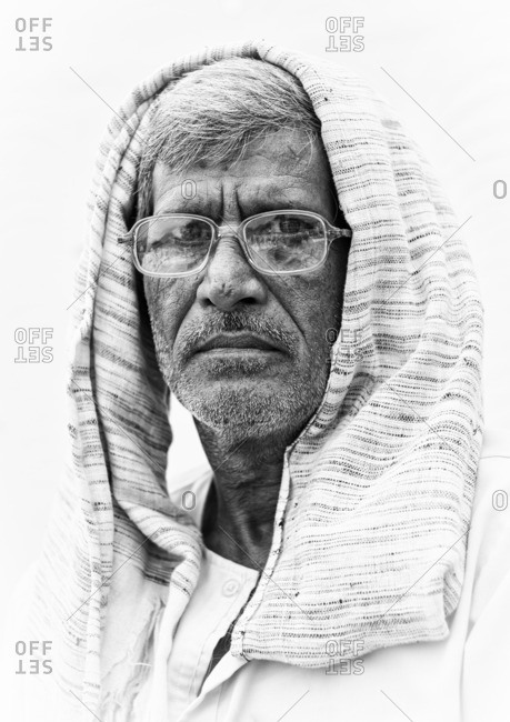 Delhi, India - November 8, 2015: Portrait of an Indian man with glasses and scarf over his head