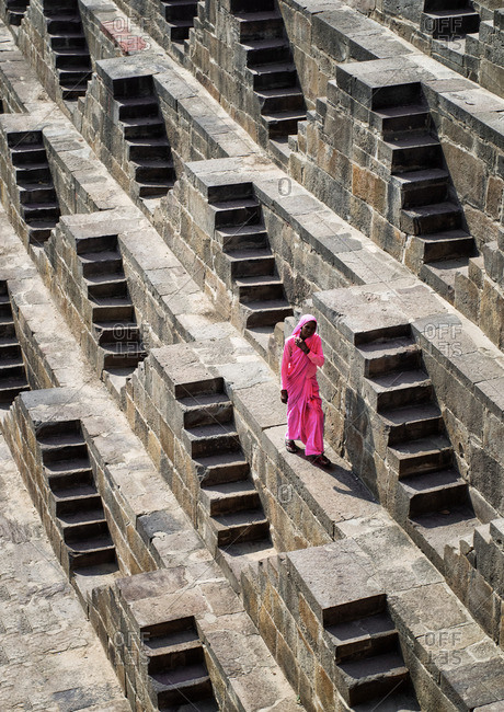 Chand Baori Step Well, Rajasthan, India - November 13, 2015: Woman walking in a step well in India