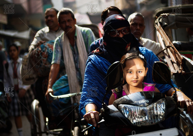 Varanasi, India - November 16, 2015: Child riding on motorized scooter with her mother