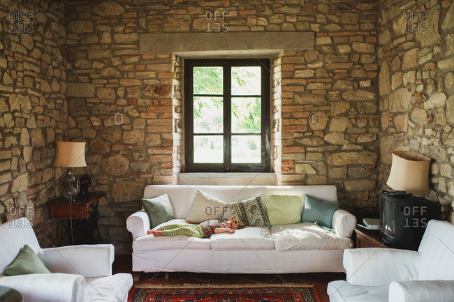 A girl taking a nap on a sofa in an old farm house