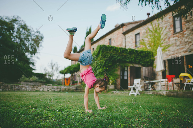 Young girl doing a cartwheel in front of an old house