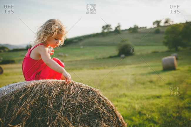 A girl sitting on a bale of hay wearing a pink dress