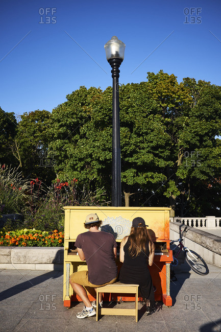 Montreal, Quebec, Canada - September 19, 2016: Young couple playing a colorful piano