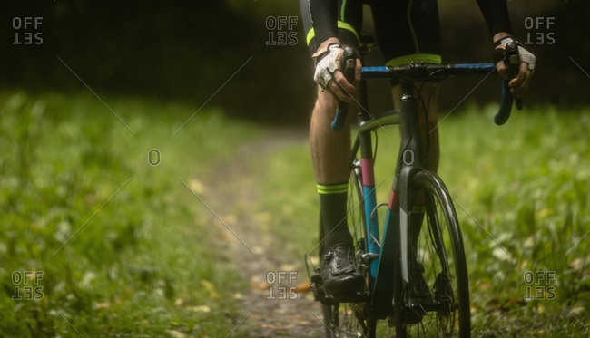 Athlete cycling on dirt track in forest