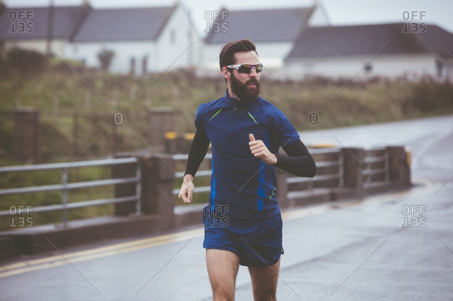 Athlete running on road during the day