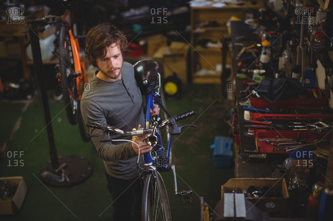 Mechanic carrying a bicycle in bicycle workshop
