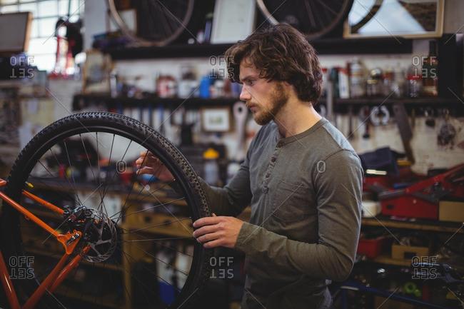 Mechanic examining a bicycle wheel in workshop