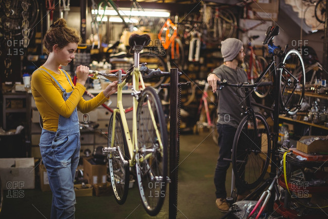 Mechanic repairing a bicycle handle bar in bicycle workshop