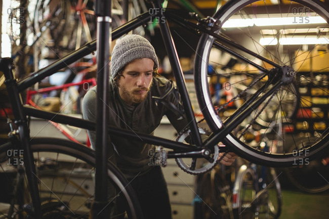 Mechanic examining a bicycle in bicycle workshop