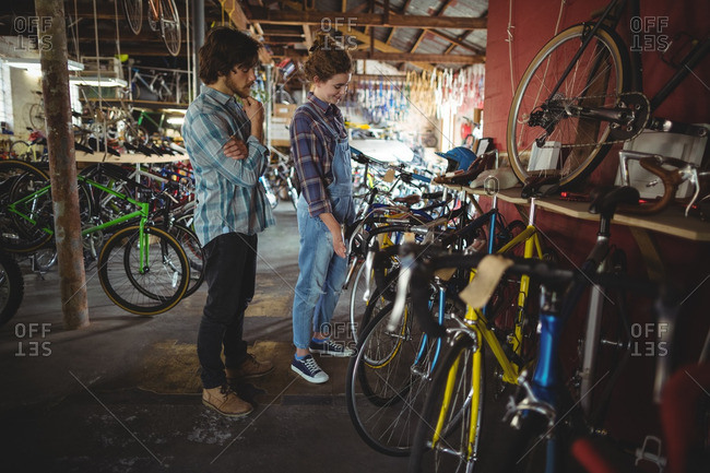 Mechanics examining a bicycle in bicycle workshop