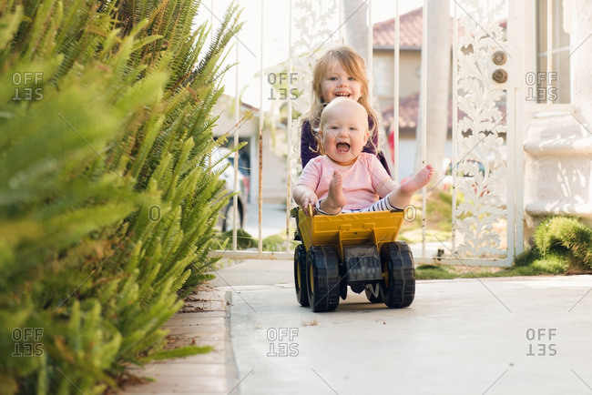Sisters playing on a toy truck