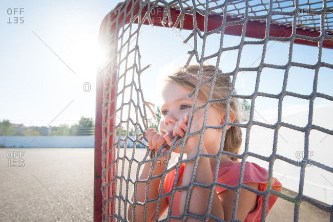 Girl staring through torn soccer net