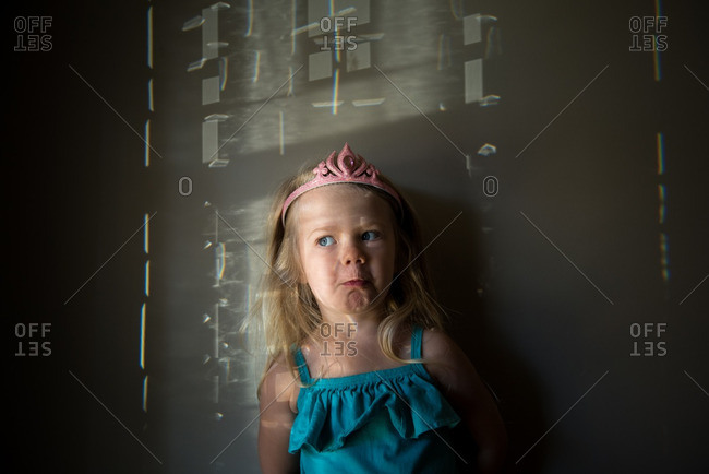 Girl in toy tiara by wall