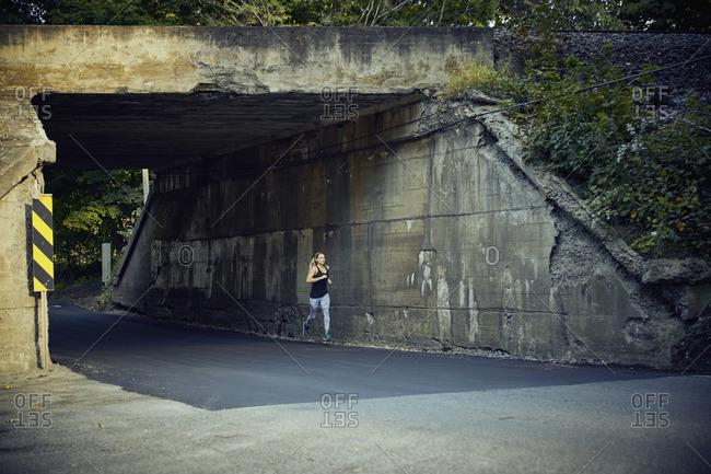 Woman jogging under train overpass