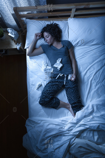 Woman sleeping surrounded by tissues
