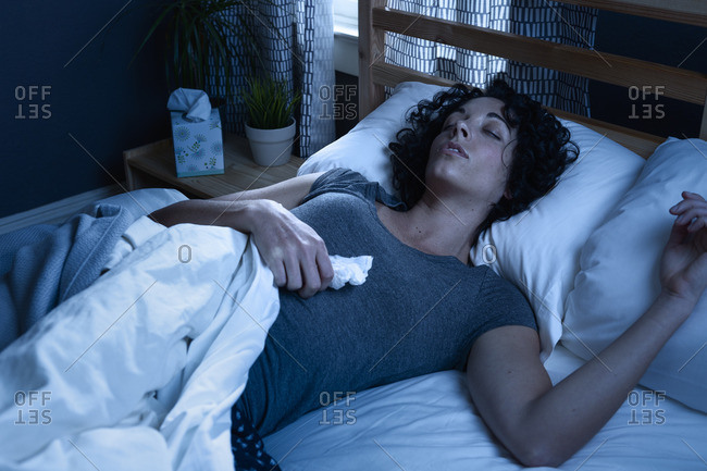 Woman holding tissue lying in bed