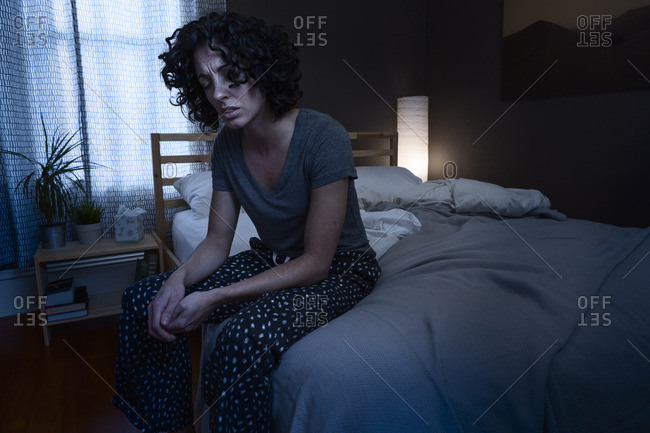 Woman sitting in bed looking sick