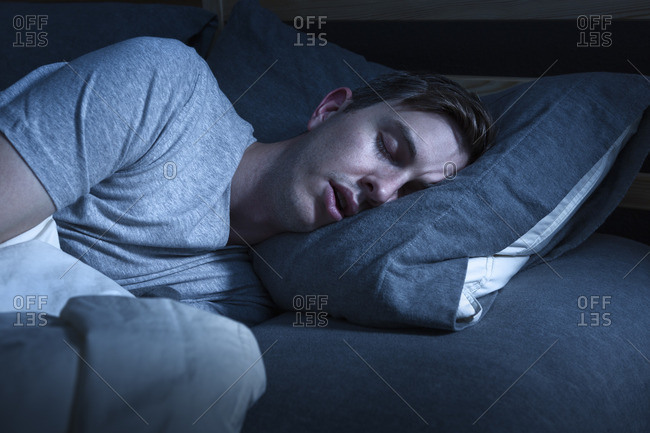 Man lying asleep in bed at night