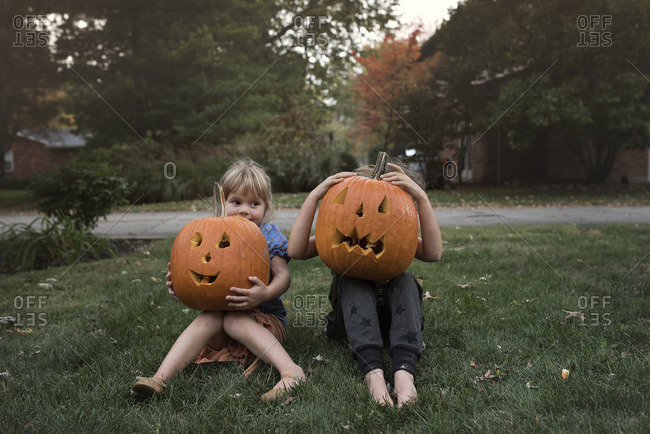 Two young children pose with their jack o'lanterns on front lawn