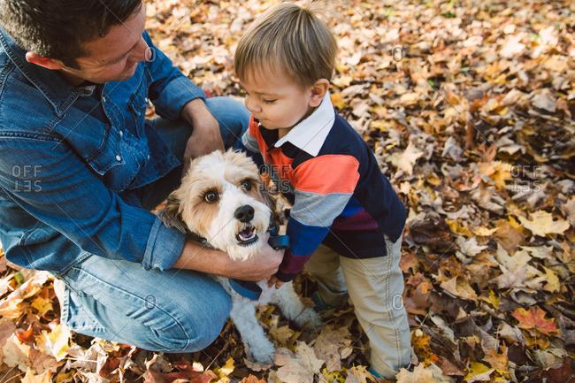 Man and toddler hugging dog