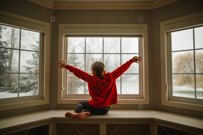 Boy throwing his arms in the air while looking out a window in winter