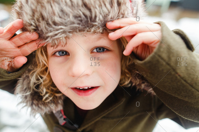 Boy with curly hair standing outside on a winter day