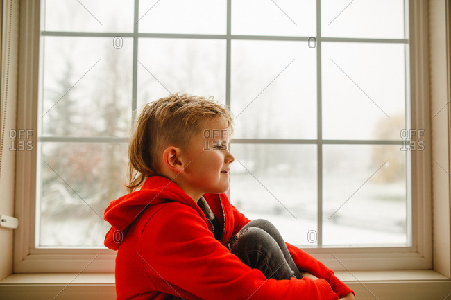 Boy with mohawk sitting by a window in winter