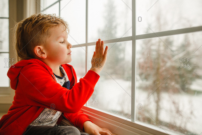 Boy with mohawk  touching window in winter