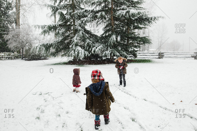 Three siblings playing outside together on a snowy day