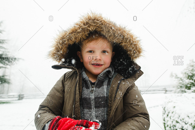 Portrait of a boy with a furry jacket hood standing outside on a winter day