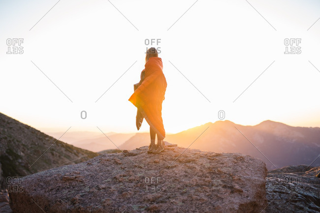 Woman wrapped in a sleeping bag overlooking sunrise in the mountains