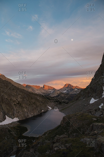 Moon in the sky at sunset over mountain landscape