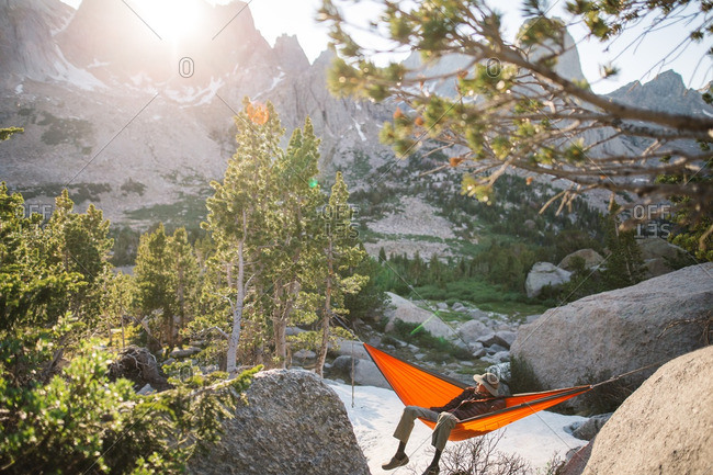 Person relaxing in a hammock at sunrise in the mountains