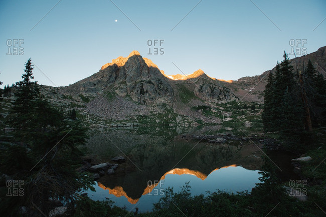 Moon in the sky at sunset over lake and mountain landscape