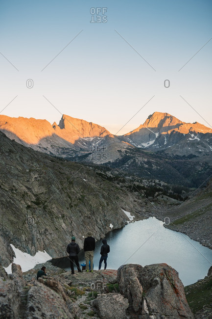 Group of people overlooking mountains and lake at sunrise