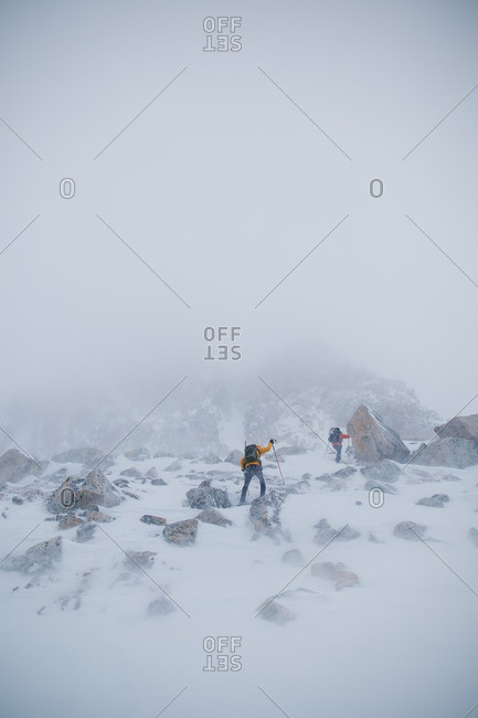 Hikers trekking through snowy mountains