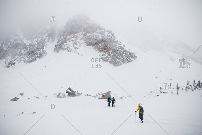 Group of hikers trekking through snowy mountains
