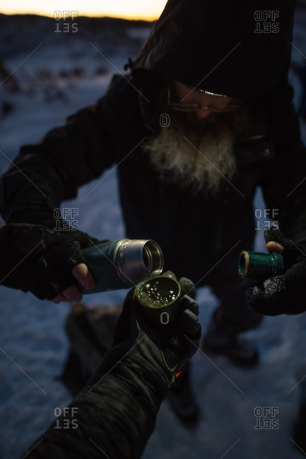 Men drinking from insulated container while hiking in snowy mountains