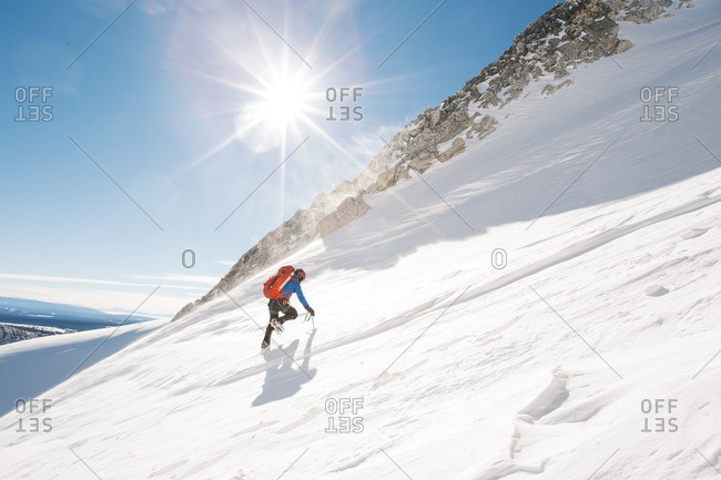Person hiking up snowy mountains on a sunny day