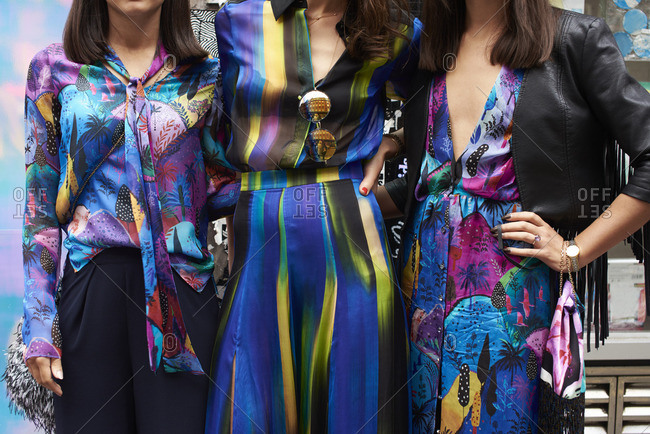 Women wearing colorful silky clothes with their hands on their hips in London