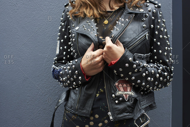 Mid section detail of woman in studded leather bike jacket