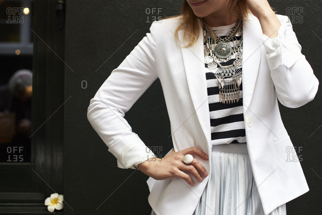 Woman in white jacket and necklace with her hand on hip
