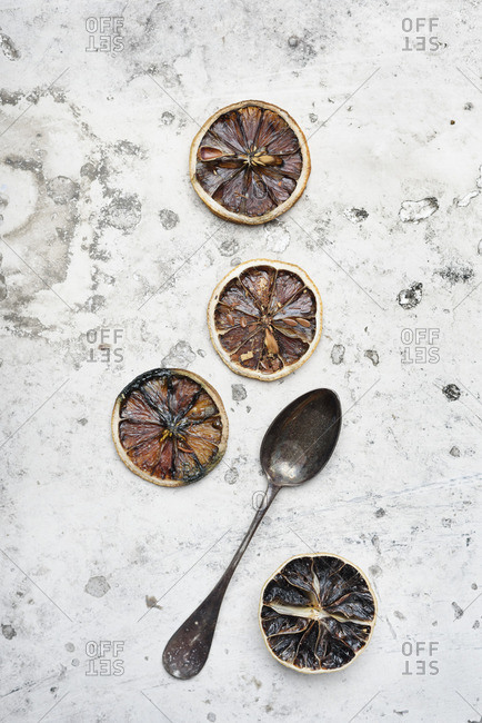 Top view of dried lemon slices and vintage spoon on dirty white background