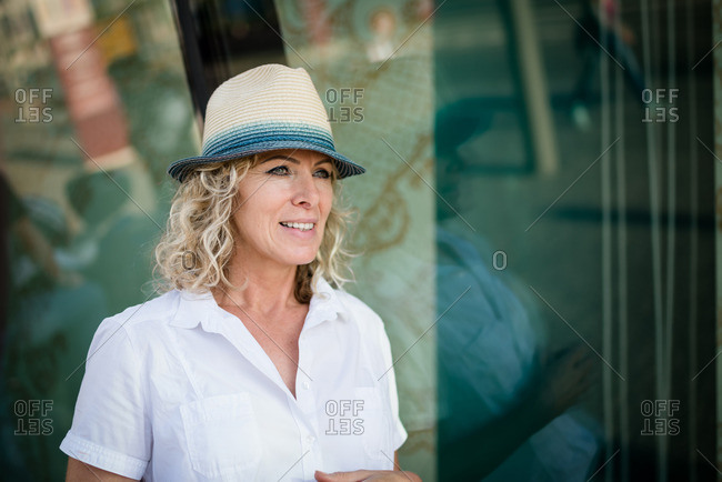 Portrait of a beautiful curly haired woman wearing hat